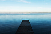 'A wooden dock leading out to a misty tranquil lake in Riding Mountain National Park; Wasagaming, Manitoba, Canada'