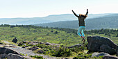 'A young woman jumps from a rock with arms in the air; St. John's, Newfoundland and Labrador, Canada'