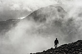 'A man walks out of the clouds from the summit of Maol Chean-dearg; Torridon, Scotland'