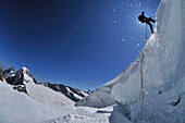 mountaineer is abseiling over the Randkluft of a glacier, Jungfrau (4158 m), Bernese Alps, Switzerland
