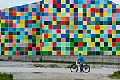Cyclist passing a building with colorful squares, Nuuk, Greenland