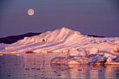 Full moon above fishing boat in front of icebergs in twilight, Ilulissat Icefjord, Ilulissat, Qaasuitsup, Greenland