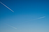 Three airplanes in a clear blue sky leaving condensation tracks, Munich, Bavaria, Germany