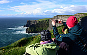 People taking photographs at the Cliffs of Moher, Clare, West coast, Ireland