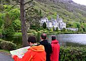 Drei Männer bei Kylemore Abbey im Connemara, Irland