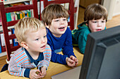 Three boys looking at a computer screen