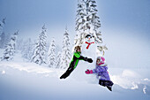Children embracing a snowman, Passo Monte Croce di Comelico, South Tyrol, Italy