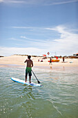 Stand-up paddler near Water Sports Centre, Martinhal Beach, Sagres, Algarve, Portugal, southernmost region of mainland Europe