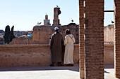Moroccan couple watching storks at Badi Palace, Saadit graves, Marrakech, Morocco