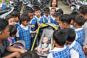 Many Balinese schoolchildren being curious about western baby, girl 5 months old, sitting in a stroller, kids gathering around, intercultural contact, meeting locals, family travel in Asia, parental leave, MR, Ubud, Bali, Indonesia