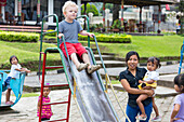 German boy on a slide, playing with Balinese kids and women, playground at the temple Pura Ulun Danau Bratan, intercultural contact, meeting locals, family travel in Asia, parental leave, German, European, MR, Ubud, Bedugul, Bali, Indonesia