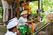 Balinese kids playing with German young boy, 3 years old, traditional clothes at temple ceremony, Balinese religion, stroller, intercultural contact, meeting local people, locals, family travel in Asia, parental leave, German, European, MR, Munduk, Bali,