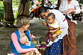 Balinese mother with her children playing with Baby of German mother, baby sling, wrap, baby sling at her mother, baby 5 months old, intercultural contact, meeting local people, locals, family travel in Asia, parental leave, German, European, MR, Munduk,