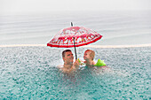 Father and son in a swimming pool, heavy rain, red umbrella, overflow pool, infinity pool, happiness, tropical rain, rainfall, sea, ocean, luxury, family travel in Asia, parental leave, German, European, MR, Amed, Bali, Indonesia