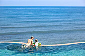Mother and son in a swimming pool, overflow pool, infinity pool, looking to the sea, happiness, sea, blue sky, luxury, paradise, family travel in Asia, parental leave, German, European, MR, Amed, Bali, Indonesia
