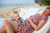 Relaxing at the beach, German mother with her baby, crawling, scrambling, canvas chair, deck chair, white, sunbed, daughter 5 months, family travel in Asia, parental leave, German, European, MR, Gili Air, Gili Inseln, Lombok, Indonesia
