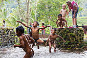 Indonesian children playing in the water, little creek, jumping, splashing water, fun, German mother and son watching, boy 3 years old, countryside, contact with local people, intercultural, family travel in Asia, parental leave, German, European, MR, Tet