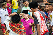 German little boy playing with Indonesian kids, children, boy 3 years old, trying their hat, fez, Islam, thumbs up, contact with local people, intercultural, family travel in Asia, parental leave, German, European, MR, Tetebatu, Lombok, Indonesia