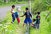 German little boy playing with Indonesian kids, crossing over a ditch, trench, giving a helping hand, soccer t-shirts,  children, countryside, village, boy 3 years old, contact with local people, intercultural, family travel in Asia, parental leave, Germa