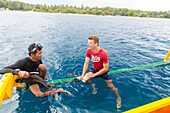Indonesian and German man in the water, snorkel, snorkelling trip, traditional boat, sitting on beam,  contact with local people, intercultural, tropical island, holiday, family travel in Asia, parental leave, German, European, MR, Gili Air, Gili Inseln,