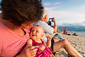 Grandmother with her granddaughter at the beach, sunset, laughing, smile, baby 5 months old, girl, grandfather taking pictures, tropical island, family travel in Asia, parental leave, German, European, MR, Gili Air, Gili Inseln, Lombok, Indonesia