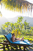 Father and daughter at swimming pool, baby, girl 5 months old, sunbed, lounger, palm trees, evening sun, playing, mountains, hotel, Balinese holiday resort, family travel in Asia, parental leave, German, European, MR, Sidemen, Bali, Indonesia