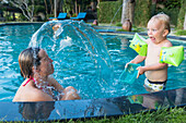 Mother and son playing in a swimming pool, son splashing water at his mum, surprise, swimmies, armbands, 3 years old, Balinese holiday resort, family travel in Asia, parental leave, German, European, MR, Sidemen, Bali, Indonesia