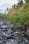 Father and son taking a bath in a river, riverbed, rocks, stones, local Balinese taking baths here, trees, local custom, intercultural, boy 3 years old, family on holiday, family travel in Asia, parental leave, German, European, MR, Sidemen, Bali, Indones