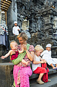 Mother with her children sitting on stairs, temple, baby 5 months old, baby sling, wrap, boy 3 years old, blond, temple Goa Lawah with bat cave, Balinese people, temple ceremony, intercultural contact, meeting local people, locals, family travel in Asia,