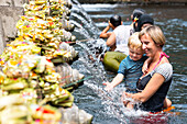 Holy springs Pura Tirta Empul, mother with her son on her arm taking a bath, pool, splashing water, water spilling pipes, tourists, temple, intercultural contact, locals, family travel in Asia, parental leave, German, European, MR, Ubud, Bali, Indonesia