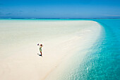 A woman opening her arms in delight on a sand bank at One Foot Island in Aitutaki Lagoon, Aitutaki, Cook Islands, South Pacific