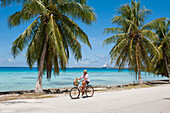 Man riding his bicycle along a road with palm trees, expedition cruise ship MS Hanseatic (Hapag-Lloyd Cruises) at anchor in the distance, Fakarava, Tuamotu Islands, French Polynesia, South Pacific