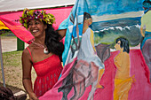 Polynesian woman with flower headdress displaying a Gaugain style pareu cloth for sale at a market, Atuona, Hiva Oa, Marquesas Islands, French Polynesia, South Pacific