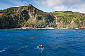 Zodiac raft from expedition cruise ship MS Hanseatic (Hapag-Lloyd Cruises) and rugged island coastline, Pitcairn, Pitcairn Group of Islands, British Overseas Territory, South Pacific