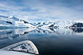 Bug von Expeditions-Kreuzfahrtschiff MS Hanseatic (Hapag-Lloyd Kreuzfahrten) vor eisbedeckter Bergkulisse mit Spiegelung, Neko Harbour, Grahamland, Antarktis
