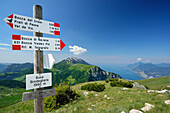 Signpost, Monte Baldo and lake Garda in background, Monte Altissimo, Garda Mountains, Trentino, Italy