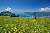 Woman hiking through flower meadow, Monte Baldo and lake Garda in background, Monte Altissimo, Garda Mountains, Trentino, Italy