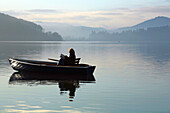 A woman sitting in a small dinghy fishing boat on Lake Edersee in Kellerwald-Edersee National Park reading a book in the morning light, Lake Edersee, Hesse, Germany, Europe