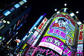 Brightly lit advertising on a busy street corner at night, Tokyo, Kanto Region, Honshu, Japan