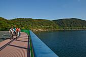 A group of cyclist riding along the Ederseerandstrasse at Lake Edersee in Kellerwald-Edersee National Park, Lake Edersee, Hesse, Germany, Europe