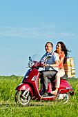 A man and a woman transporting a stack of books on a red Vespa scooter, Bad Wildungen, Hesse, Germany, Europe