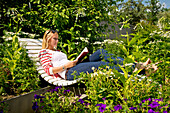 A young blond woman lying on a bench in Kurpark Bad Wildungen reading a book, Bad Wildungen, Hesse, Germany, Europe