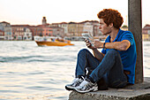 A red-haired young man sitting on the banks of the Canale della Giudecca in Dorsoduro drawing, Venice, Veneto, Italy, Europe