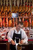 Vendor selling Jamon ham in Mercado de San Miguel, Madrid, Spain