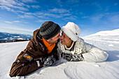 Couple lying in snow, Zirbitzkogel, Muehlen, Styria, Austria