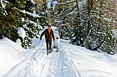 Man pulling a woman sitting on a sledge, Muehlen, Styria, Austria