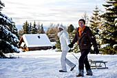 Couple pulling a sledge through snow, Muehlen, Styria, Austria