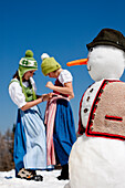 Two girls wearing dirndls, snowman in foreground, Frauenalpe, Murau, Styria, Austria