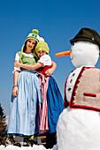 Zwei girls wearing dirndls embracing each other, snowman in foreground, Frauenalpe, Murau, Styria, Austria
