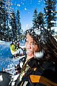 Young women having a snowball fight while tobogganing, Kreischberg, Murau, Styria, Austria